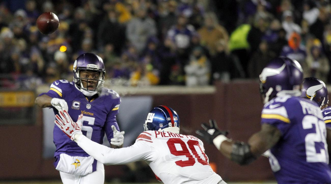 Minnesota Vikings quarterback Teddy Bridgewater (5) passes the ball to Vikings running back Adrian Peterson (28) while under pressure from New York Giants defensive end Jason Pierre-Paul (90) during the first half of an NFL football game, Sunday, Dec. 27,