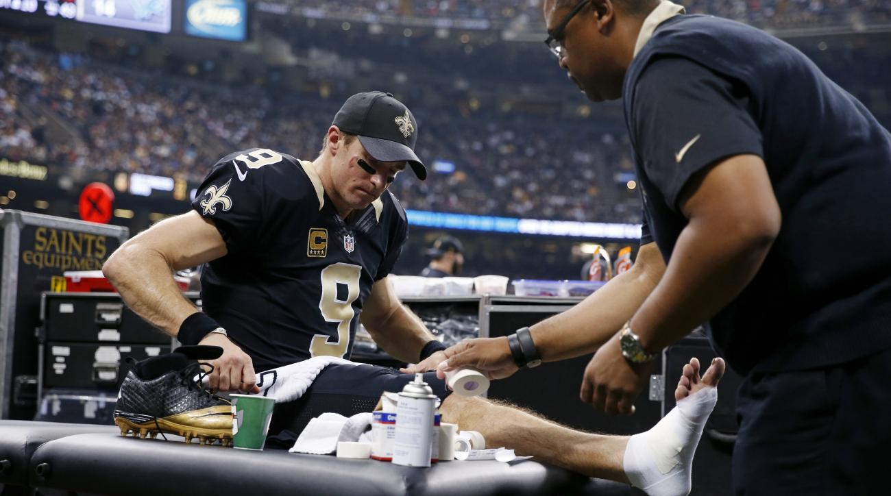 FILE - In this Monday, Dec. 21, 2015, file photo, New Orleans Saints quarterback Drew Brees has his ankle tended to during the first half of an NFL football game against the Detroit Lions in New Orleans. Brees prepares to play once more in his injured rig