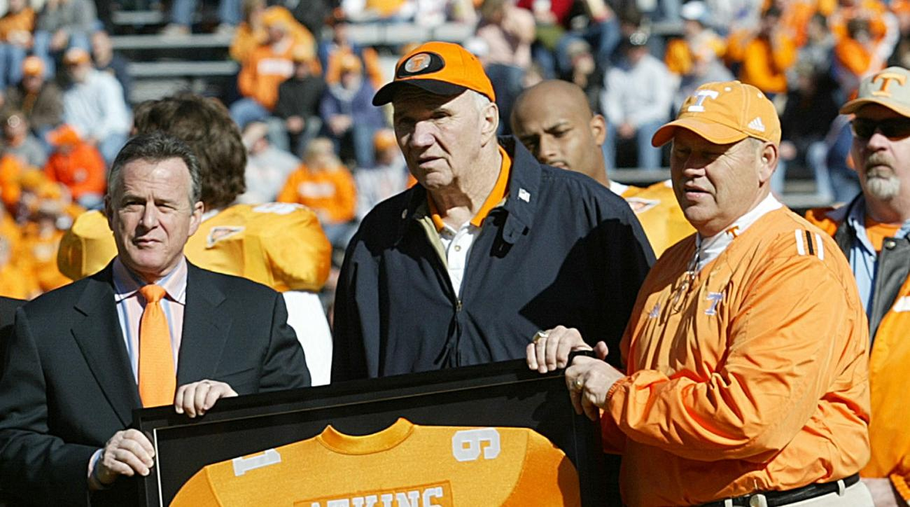 FILE - In tis Nov. 19, 2005, file photo, Tennessee coach Phillip Fulmer, right, and university president John Petersen, left, assist Doug Atkins with a framed jersey as his No. 91 was retired before Tennessee's NCAA college football game against Vanderbil