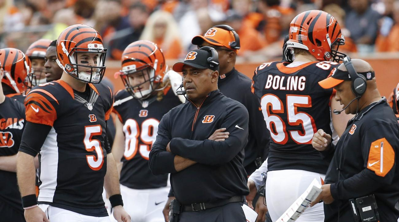 FILE - In this Sunday, Dec. 13, 2015 file photo, Cincinnati Bengals head coach Marvin Lewis, center, stands on the sideline along quarterback AJ McCarron (5) and offensive coordinator Hue Jackson, right, in the first half of an NFL football game against t