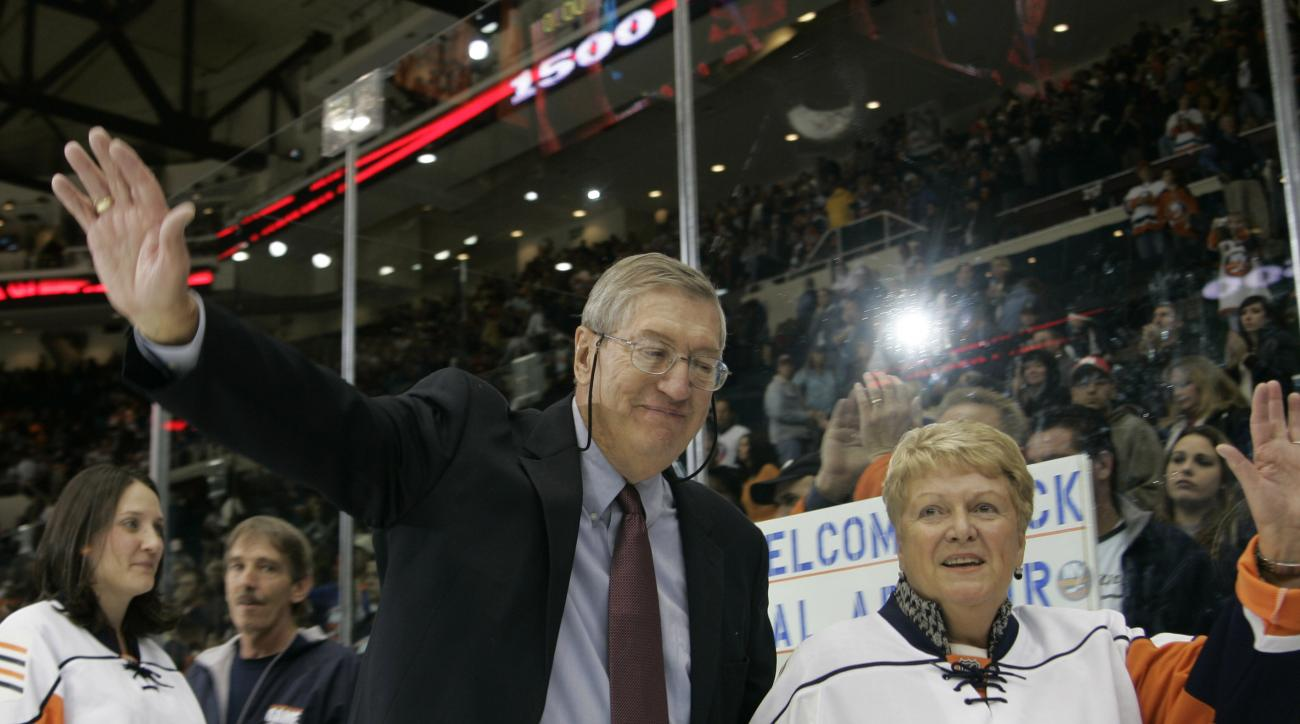 FILE - In this Nov. 3, 2007, file photo, New York Islanders head coach Al Arbour waves to fans as he leaves the ice with his wife Claire after returning to the Islanders to coach his 1500th hockey game, against the Pittsburgh Penguins at the Nassau Colise