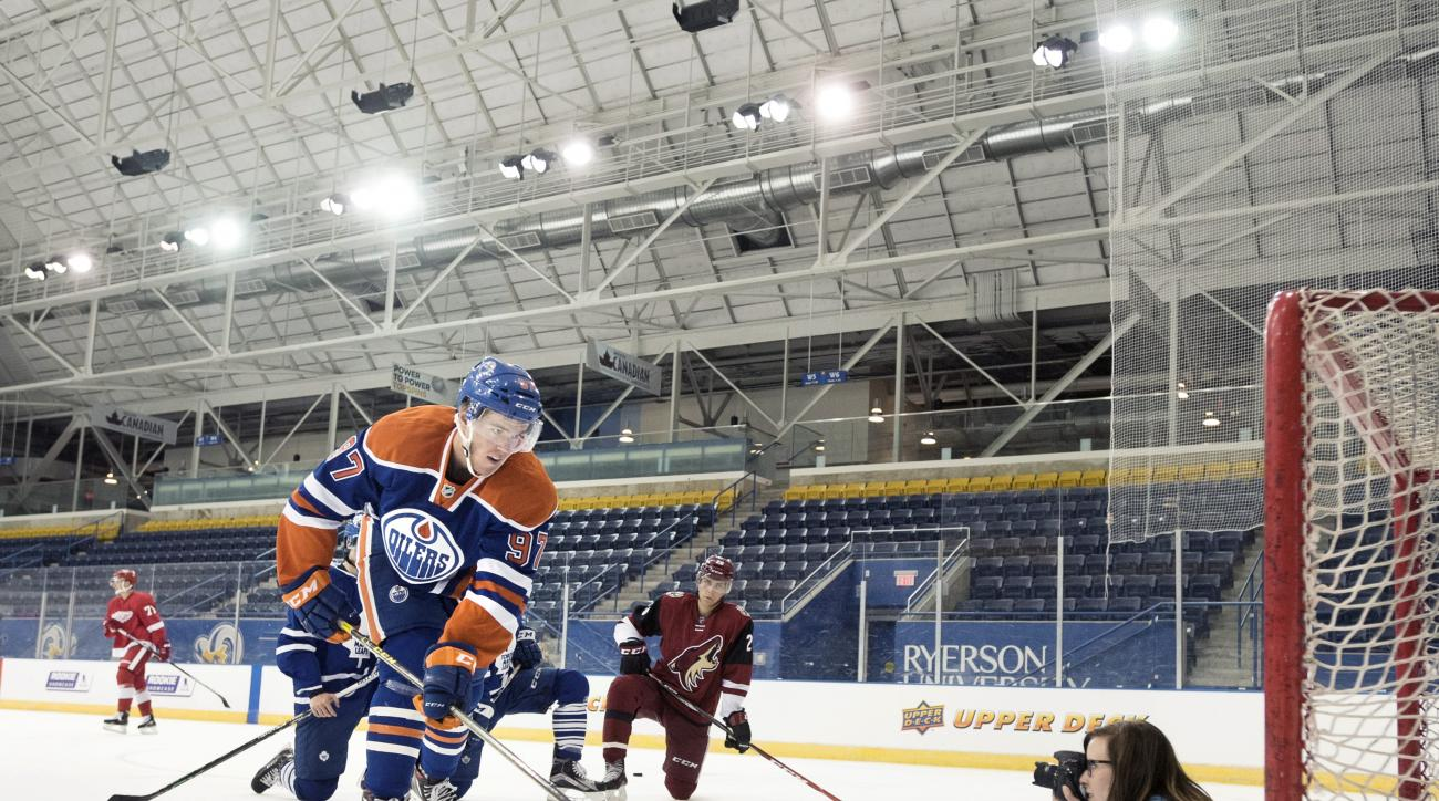 FILE - In this Tuesday, Sept. 1, 2015, file photo, Edmonton Oilers' Connor McDavid shoots a puck over a photographer during the National Hockey League Players Association (NHLPA) Rookie Showcase in Toronto.  All eyes are on the 18-year-old forward, a can'