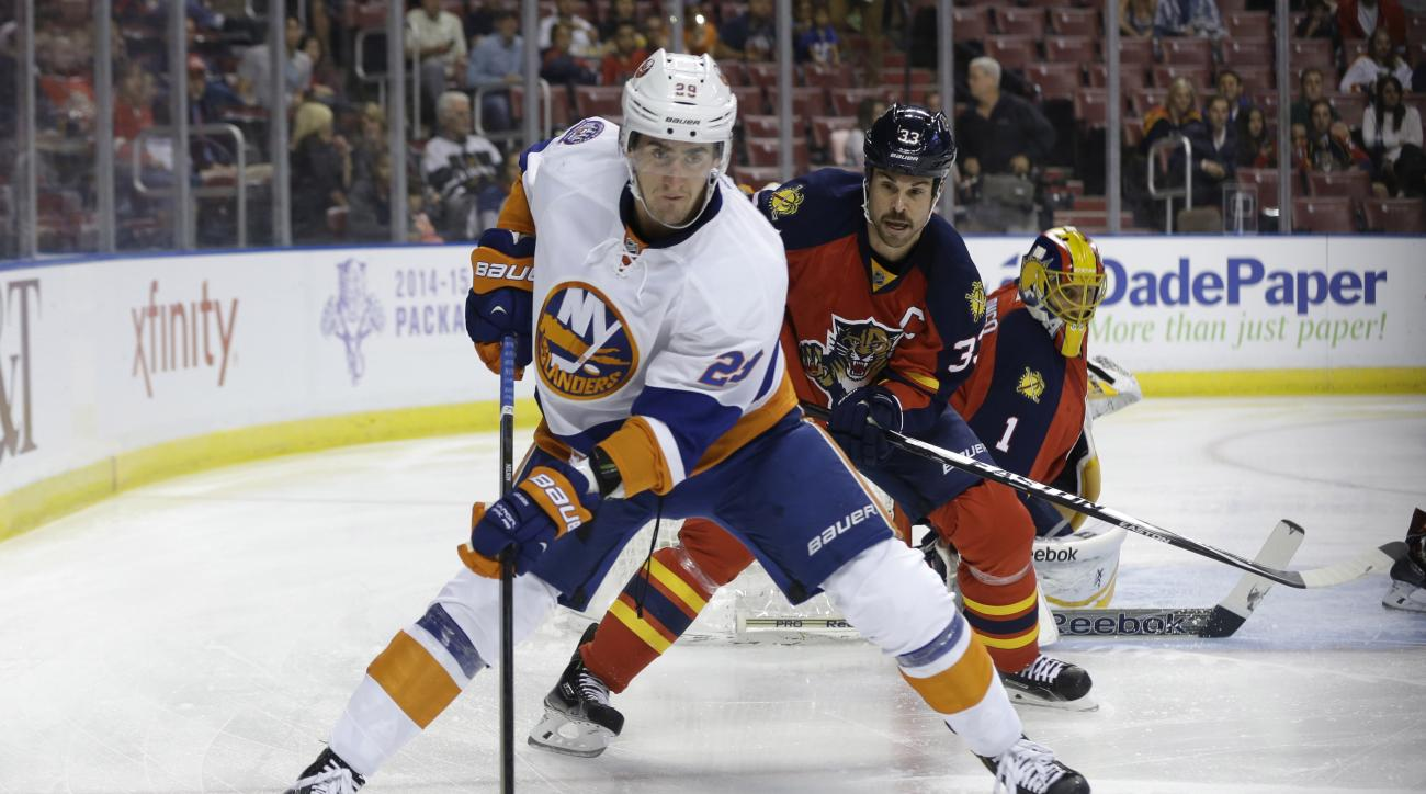 FILE - In this Friday, Nov. 14, 2014 file photo, New York Islanders center Brock Nelson (29) and Florida Panthers defenseman Willie Mitchell (33) go for the puck in the first period of an NHL hockey game in Sunrise, Fla. The New York Islanders re-signed c