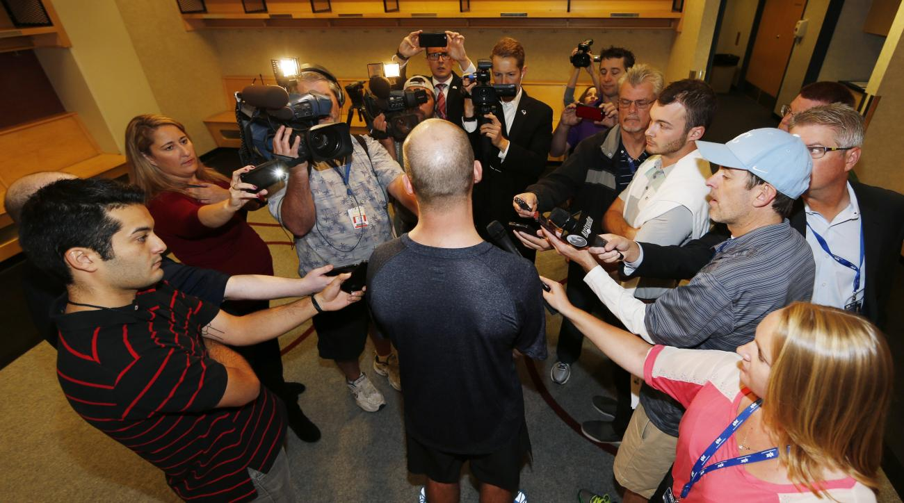 Colorado Avalanche right wing Blake Comeau, front center, is surrounded by reporters as players report for the first day of NHL hockey training camp, Thursday, Sept. 17, 2015, in Denver. Players will take to the ice Friday for practice sessions to kick of