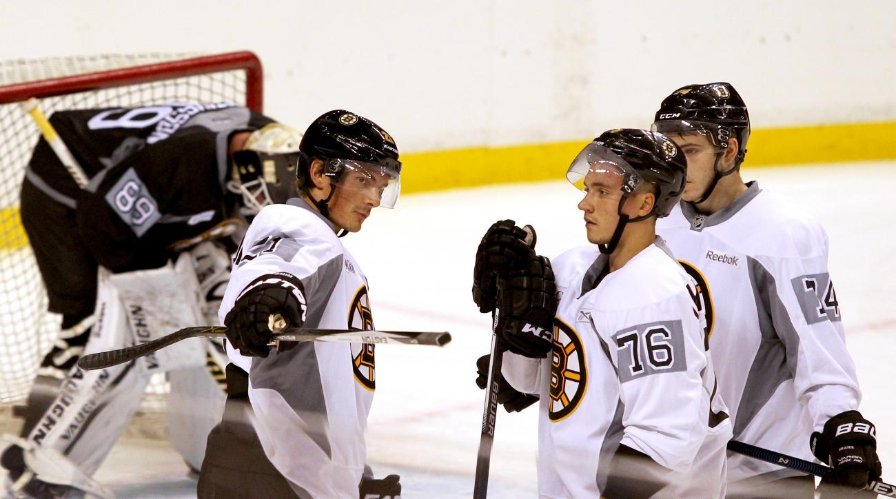 Boston Bruins' Loui Ericsson, (21), of Sweden, explains a drill to Alex Khokhlachev (76), of Russia, on the first day the full team skated during an NHL training camp practice at TD Garden, Friday, Sept. 18, 2015, in Boston.  (AP Photo/Mary Schwalm)