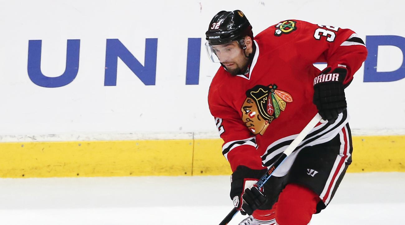 Chicago Blackhawks defenseman Michal Rozsival (32) looks to pass the puck against the Vancouver Canucks during the first period of an NHL hockey game Thursday, April 2, 2015, in Chicago. The Blackhawks won 3-1. (AP Photo/Kamil Krzaczynski)