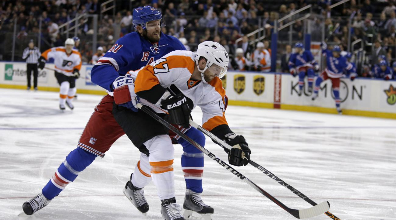Philadelphia Flyers defenseman Andrew MacDonald (47) battles for the puck with New York Rangers left wing Rick Nash (61) during the second period of an NHL preseason hockey game at Madison Square Garden in New York, Monday, Sept. 28, 2015. (AP Photo/Adam