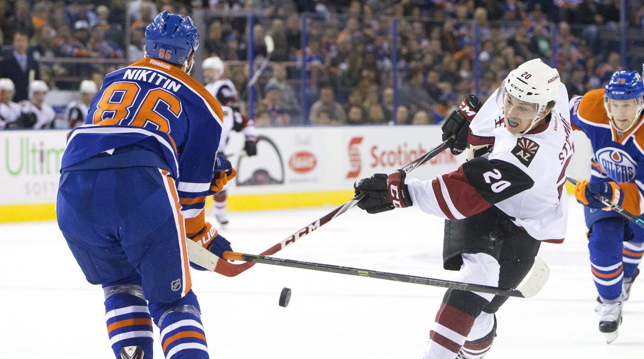 Arizona Coyotes' Dylan Strome's, right, shot is blocked by Edmonton Oilers' Nikita Nikitin (86) during the first period of a preseason NHL hockey game in Edmonton, Alberta, Tuesday, Sept. 29, 2015. (Jason Franson/The Canadian Press via AP) MANDATORY CREDI