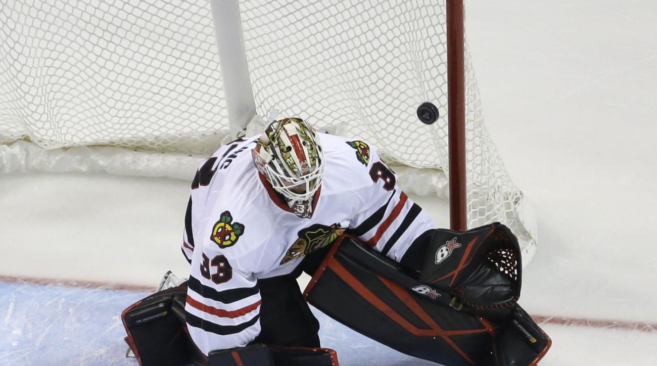 St. Louis Blues' Kyle Brodziak, bottom, scores past Chicago Blackhawks goalie Scott Darling during the third period of an NHL preseason hockey game Thursday, Oct. 1, 2015, in St. Louis. The Blues won 5-2. (AP Photo/Jeff Roberson)