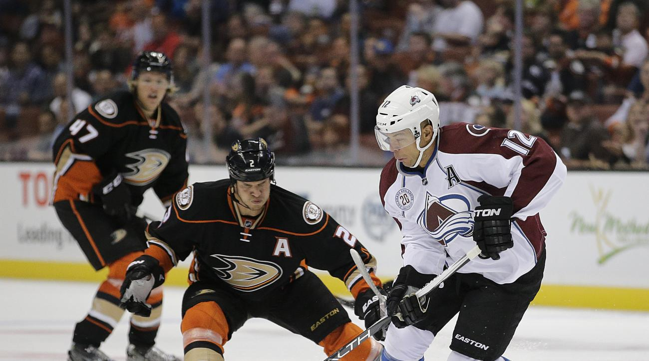 Colorado Avalanche's Jarome Iginla, right, moves the puck under pressure by Anaheim Ducks' Kevin Bieksa during the second period of an NHL preseason hockey game, Thursday, Oct. 1, 2015, in Anaheim, Calif. (AP Photo/Jae C. Hong)