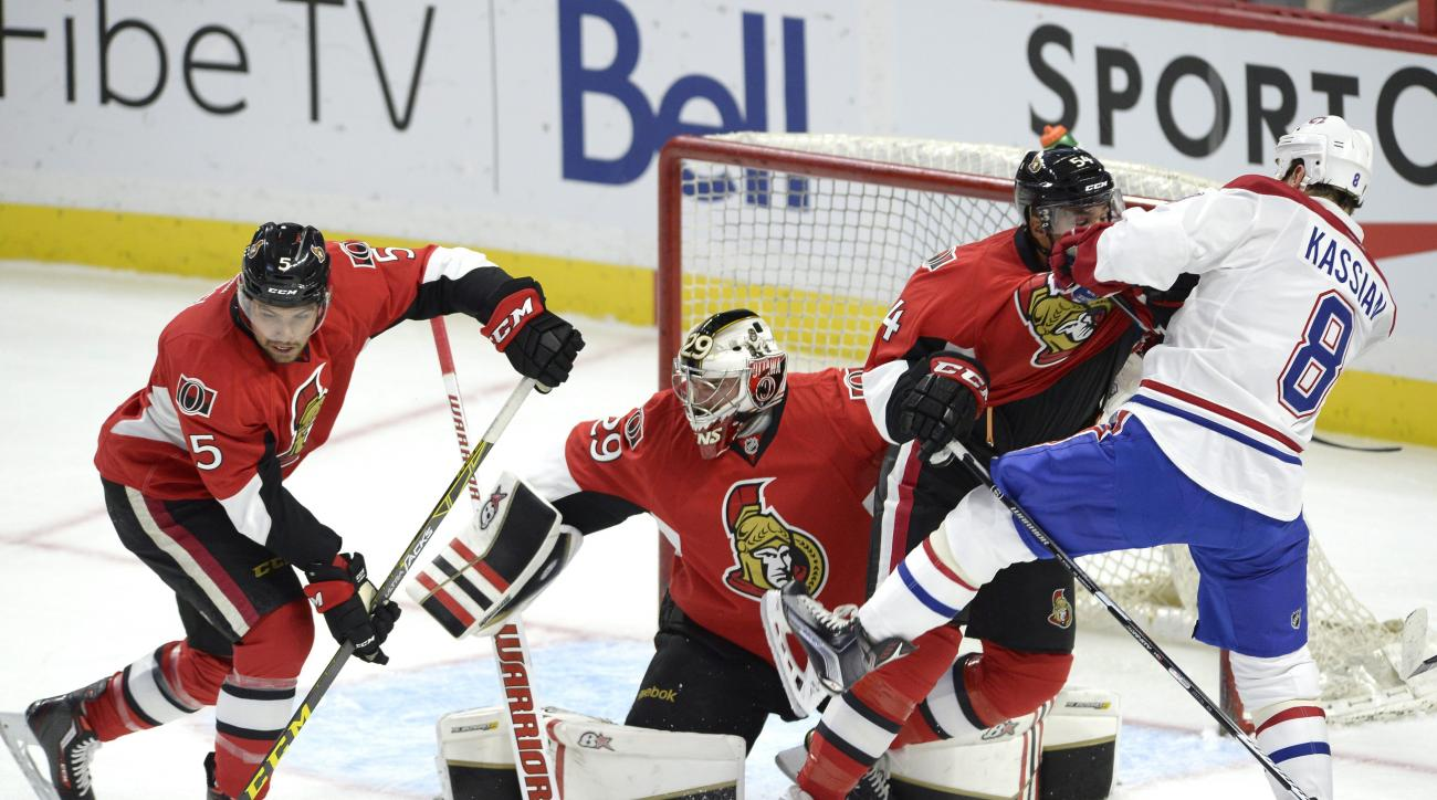 Ottawa Senators' Cody Ceci (5) clears the puck from goalie Matt O'Connor (29) as Chris Wideman (45) battles with Montreal Canadiens' Zack Kassian (8) during the first period of a pre-season NHL hockey game, Saturday Oct. 3, 2015, in Ottawa, Ontario. (Just