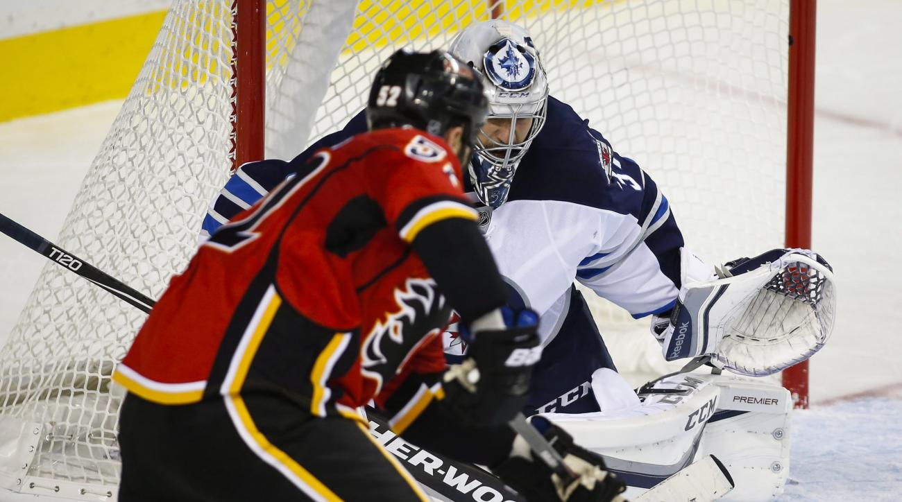 Winnipeg Jets goalie Ondrej Pavelec, right, from the Czech Republic, blocks the net on a shot from Calgary Flames' Brandon Bollig during the first period of an NHL preseason hockey game, Saturday, Oct. 3, 2015 in Calgary, Alberta. (Jeff McIntosh/The Canad