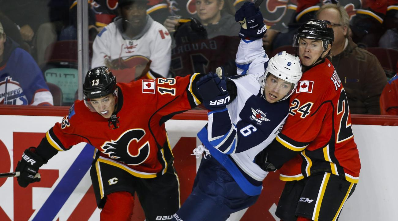 Winnipeg Jets' Alexander Burmistrov, center, from Russia, gets caught between Calgary Flames Johnny Gaudreau, left, and Jiri Hudler, from the Czech Republic, during the first period of an NHL preseason hockey game, Saturday, Oct. 3, 2015 in Calgary, Alber