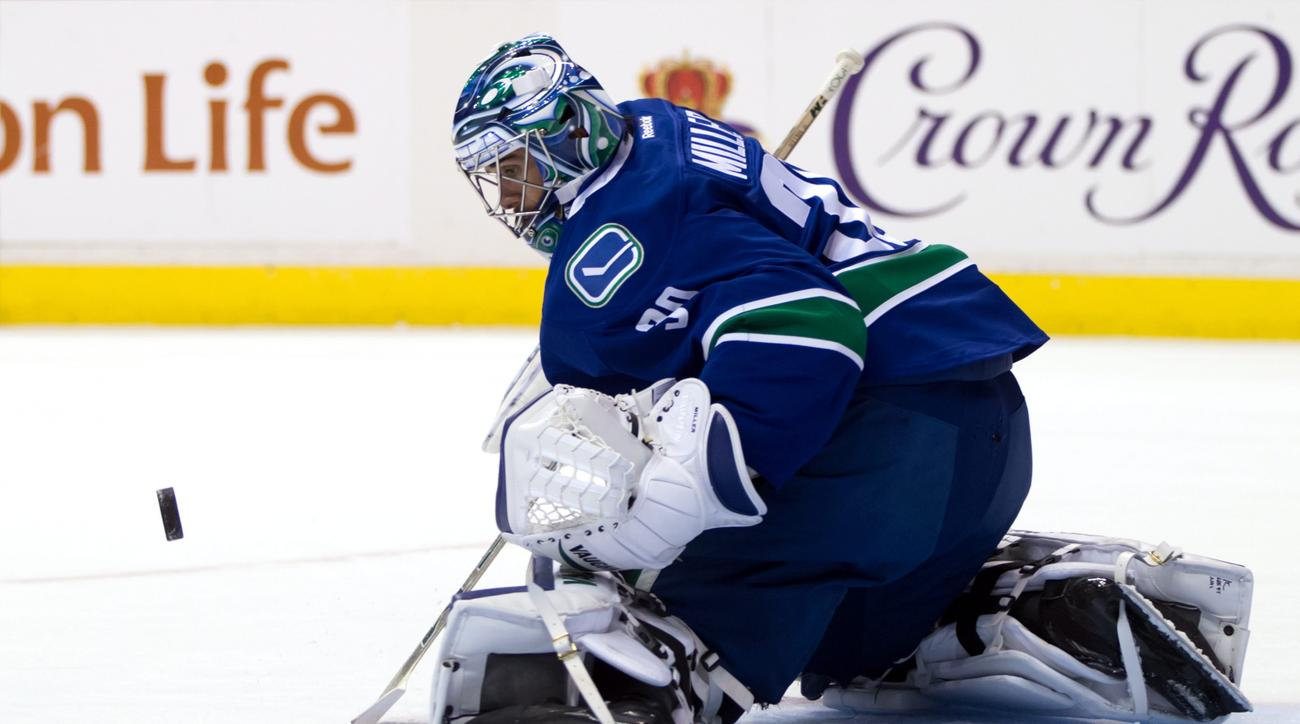 Vancouver Canucks goalie Ryan Miller makes a save against the Edmonton Oilers during the first period of a preseason NHL hockey game in Vancouver, British Columbia, Saturday, Oct. 3, 2015. (Darryl Dyck/The Canadian Press via AP) MANDATORY CREDIT