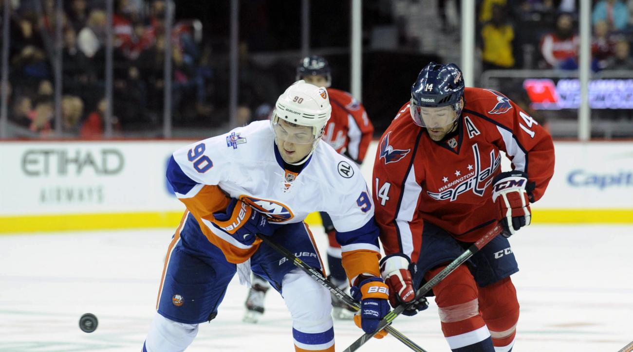 New York Islanders' Kirill Petrov (90) and Washington Capitals' Justin Williams (14) look to the puck during the first period of an NHL hockey game on Sunday, Oct. 4, 2015 in Washington. (AP Photo/Kevin Wolf)