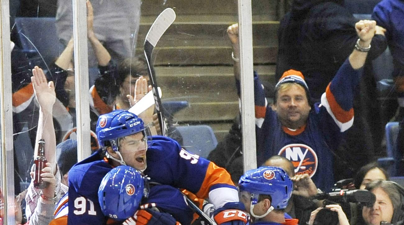 FILE - In this Dec. 22, 2010, file photo, New York Islanders center John Tavares (91) celebrates his game-winning goal against the Tampa Bay Lightning with defensemen James Wisniewski (20) and Andrew MacDonald (47) in overtime of an NHL hockey game in Uni