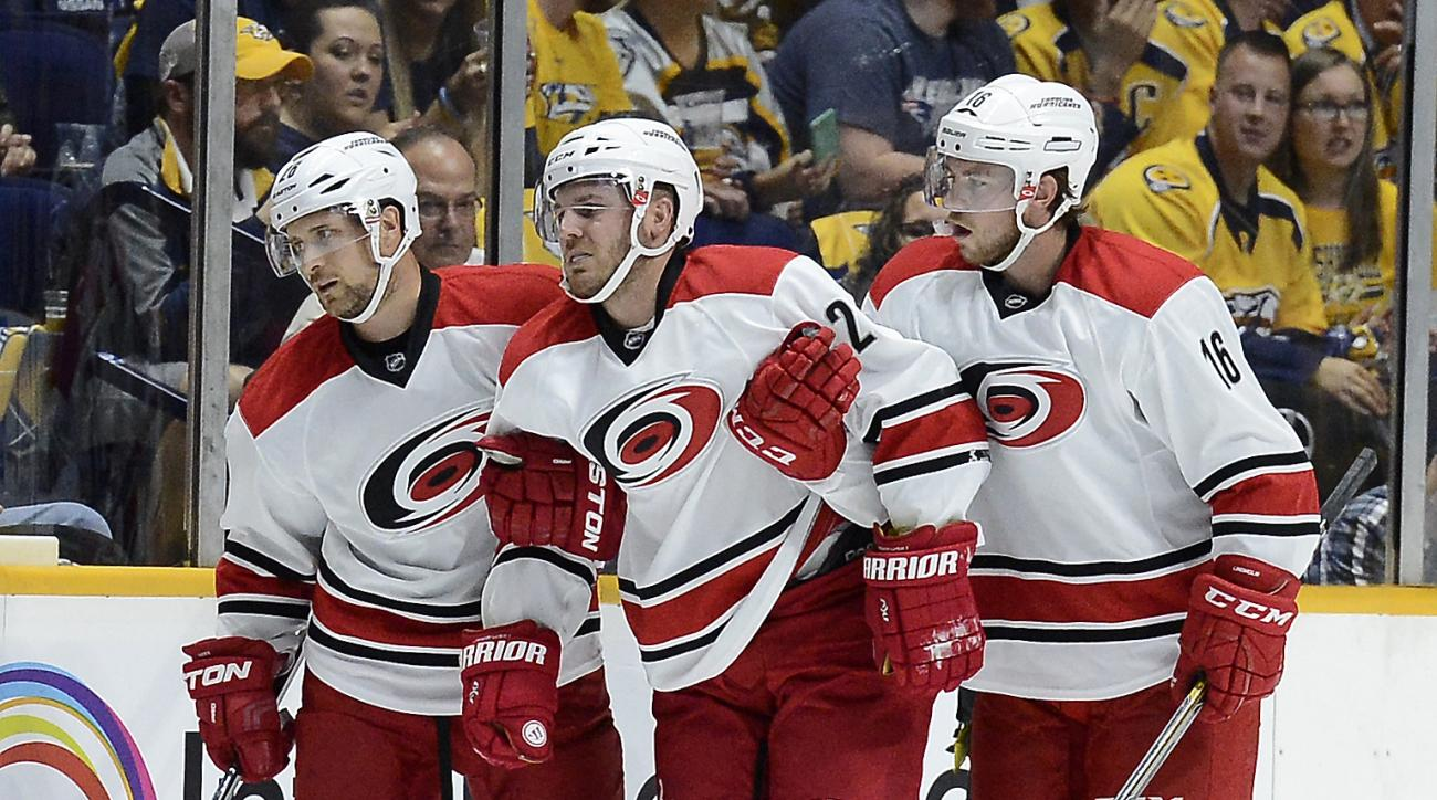 Carolina Hurricanes defenseman James Wisniewski, center, is helped off the ice by John-Michael Liles, left, and  Elias Lindholm, of Sweden, after being injured in the first period of an NHL hockey game against the Nashville Predators, Thursday, Oct. 8, 20