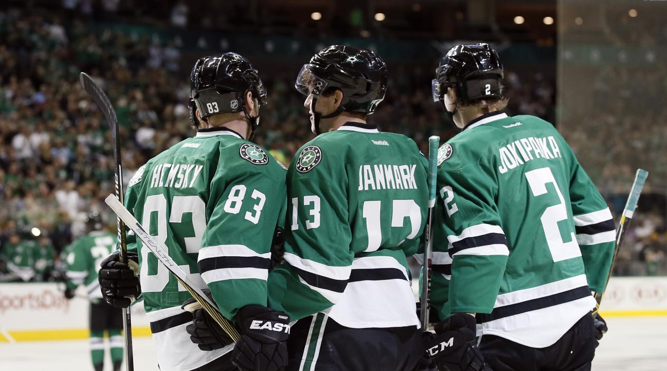 Dallas Stars' Ales Hemsky (83), of the Czech Republic, and Jyrki Jokipakka (2), of Finland, celebrate with Mattias Janmark (13), of Sweden, after Janmark scored in the first period of an NHL hockey game against the Pittsburgh Penguins, Thursday, Oct. 8, 2