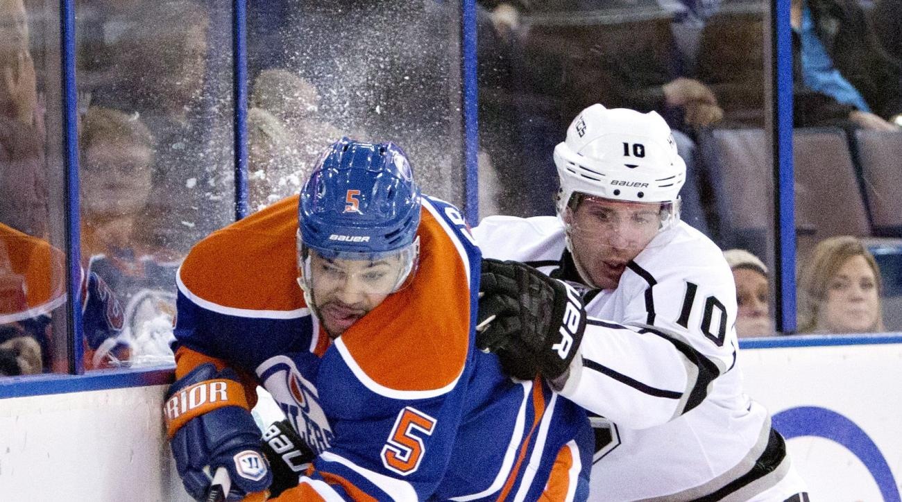 FILE - In this April 10, 2014, file photo, Los Angeles Kings' Mike Richards (10) checks Edmonton Oilers' Mark Fraser (5) during first-period NHL hockey game action in Edmonton, Alberta. Richards and the Kings have settled their dispute over the terminatio