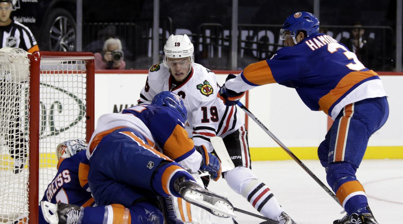Chicago Blackhawks center Jonathan Toews (19) has his shot stopped by New York Islanders goalie Thomas Greiss (1), Johnny Boychuk (55) and Travis Hamonic (3) in the first period of an NHL hockey game, Friday, Oct. 9, 2015 in New York. (AP Photo/Adam Hunge