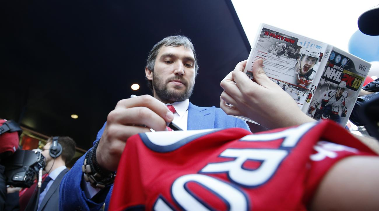 Washington Capitals left wing Alex Ovechkin, from Russia, signs an autograph for a fan as he walks a red carpet before a season-opening NHL hockey game against the New Jersey Devils, Saturday, Oct. 10, 2015, in Washington. (AP Photo/Alex Brandon)
