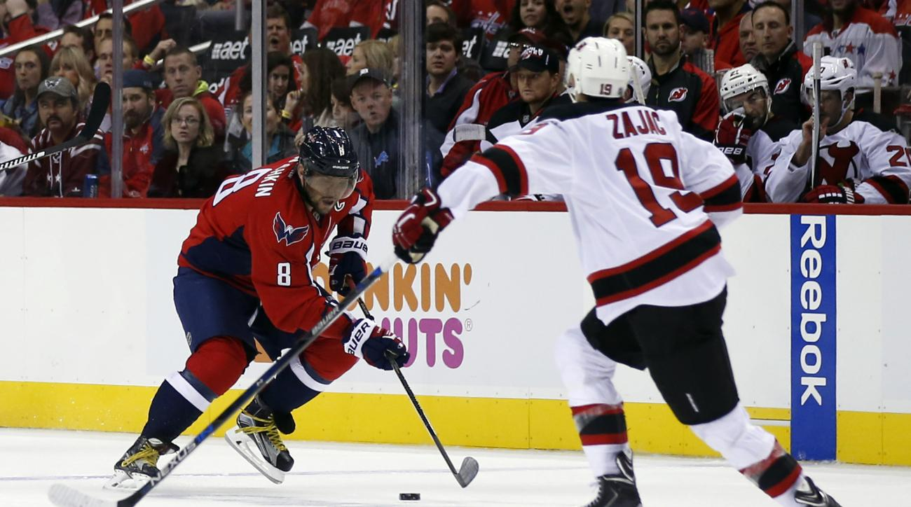 Washington Capitals left wing Alex Ovechkin (8), from Russia, skates with the puck with New Jersey Devils center Travis Zajac (19) nearby during the second period of an NHL hockey game, Saturday, Oct. 10, 2015, in Washington. (AP Photo/Alex Brandon)