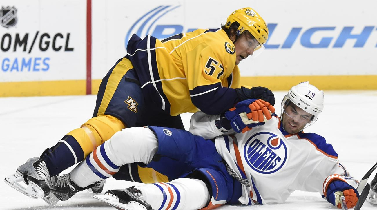 Nashville Predators left wing Gabriel Bourque (57) falls on Edmonton Oilers defenseman Justin Schultz (19) in the second period of an NHL hockey game Saturday, Oct. 10, 2015, in Nashville, Tenn. (AP Photo/Mark Zaleski)