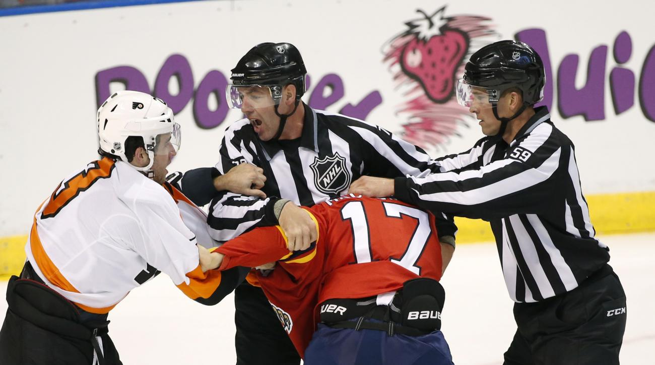 Linesmen Brian Mach, center rear, and Steve Barton (59) attempt to separate Philadelphia Flyers defenseman Brandon Manning (23) and Florida Panthers center Derek MacKenzie (17) during a fight in the second period of an NHL hockey game, Saturday, Oct. 10,