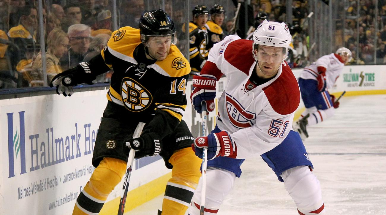 Boston Bruins right wing Brett Connolly (14) and Montreal Canadiens center David Desharnais (51) battle for the puck along the boards during the second period of an NHL hockey game in Boston, Saturday, Oct. 10, 2015. (AP Photo/Mary Schwalm)