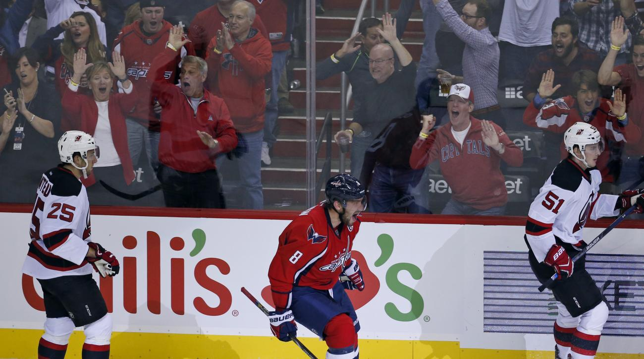 Washington Capitals left wing Alex Ovechkin (8), from Russia, celebrates his goal with New Jersey Devils centers Stefan Matteau (25) and Sergey Kalinin (51), from Russia, nearby, during the third period of an NHL hockey game, Saturday, Oct. 10, 2015, in W