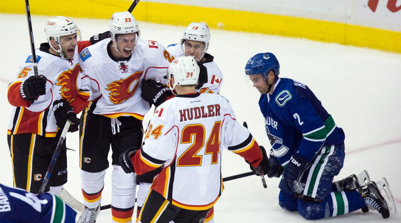 Calgary Flames' Mark Giordano (5), Sean Monahan (23), Johnny Gaudreau (13) and Jiri Hudler (24), of the Czech Republic, celebrate Monahan's goal as Vancouver Canucks' Dan Hamhuis, right, kneels on the ice during the third period of an NHL hockey game in V