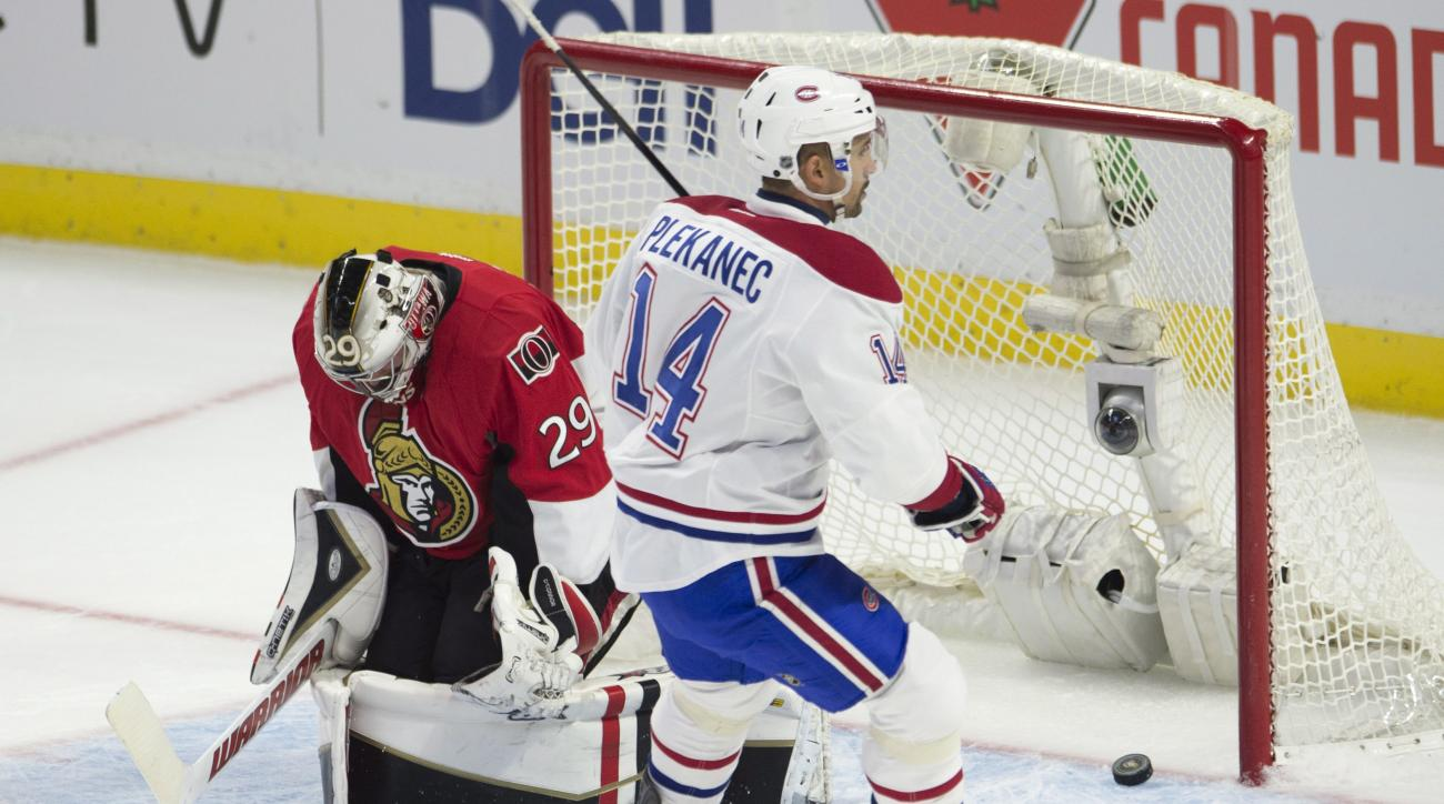 Montreal Canadiens center Tomas Plekanec puts the puck past Ottawa Senators goalie Matt O'Connor during the first period of an NHL hockey game, Sunday, Oct. 11, 2015 in Ottawa, Ontario. (Adrian Wyld/The Canadian Press via AP) MANDATORY CREDIT