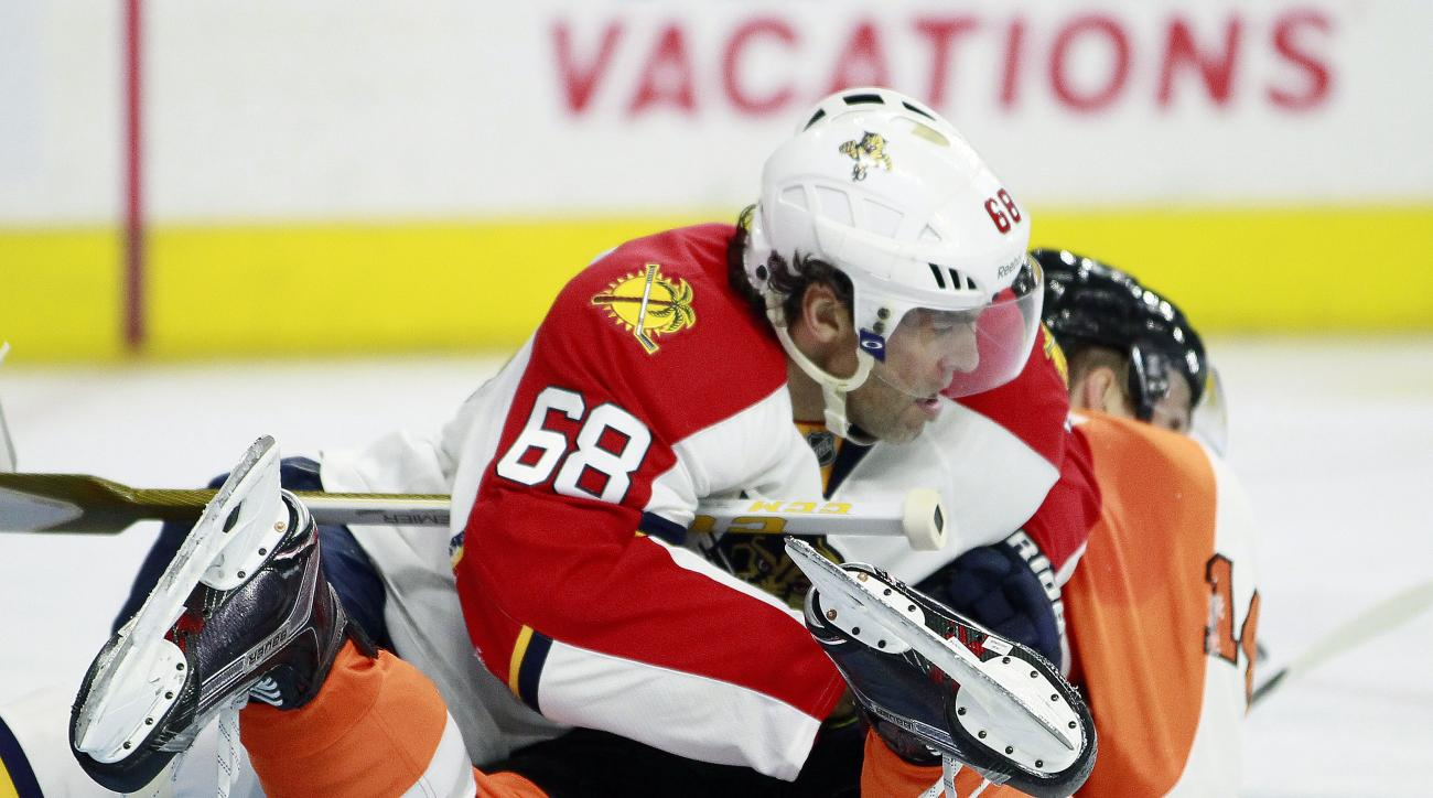 Florida Panthers' Jaromir Jagr holds Philadelphia Flyers' Sean Couturier down on the ice as the play moves away during the second period of an NHL hockey game Monday, Oct. 12, 2015, in Philadelphia. (AP Photo/Tom Mihalek)