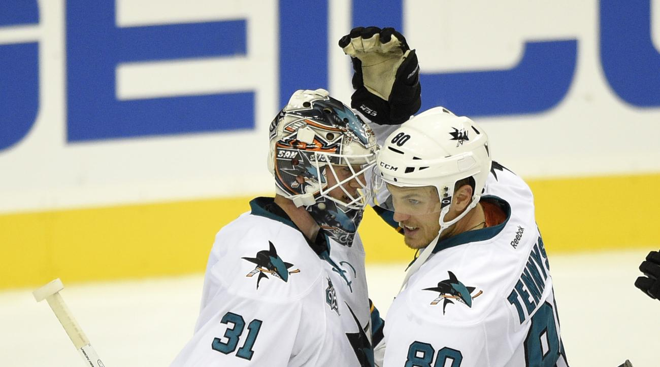 San Jose Sharks goalie Martin Jones (31) celebrates with Matt Tennyson (80) after an NHL hockey game against the Washington Capitals, Tuesday, Oct. 13, 2015, in Washington. The Sharks won 5-0. (AP Photo/Nick Wass)