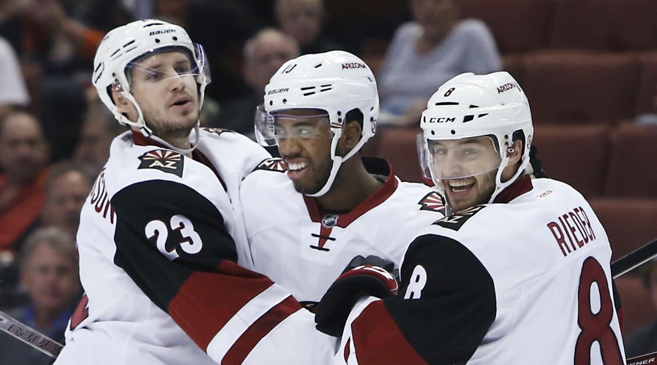 Arizona Coyotes' Oliver Ekman-Larsson (23),  Anthony Duclair and Tobias Rieder (8) celebrate a goal by Duclair during the first period of an NHL hockey game against the Anaheim Ducks in Anaheim, Calif., Wednesday, Oct. 14, 2015. (AP Photo/Christine Cotter