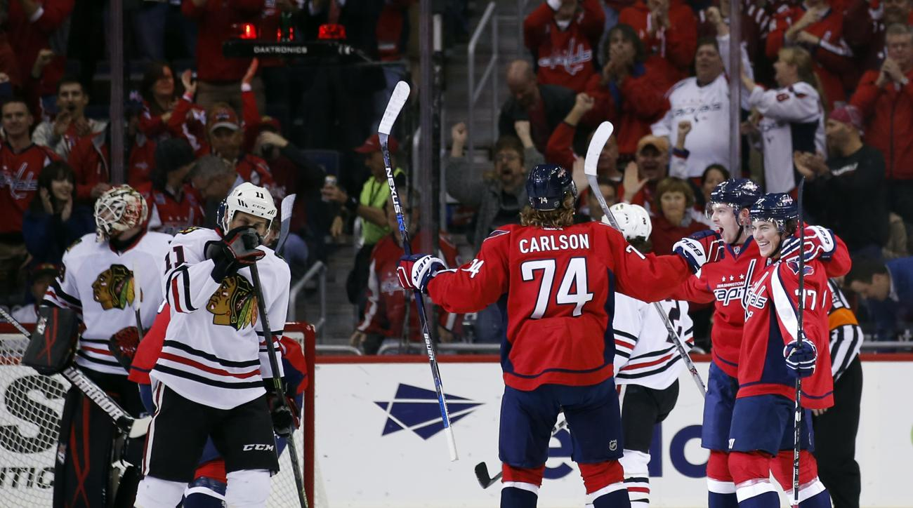 Washington Capitals right wing T.J. Oshie (77), center Evgeny Kuznetsov (92), from Russia, and defenseman John Carlson (74) celebrate Oshie's goal with Chicago Blackhawks center Andrew Desjardins (11) nearby, in the first period of an NHL hockey game, Thu
