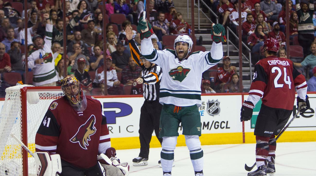 Minnesota Wild's Jason Zucker, center, reacts after Mikko Koivu scored a shorthanded goal past Arizona Coyotes' Mike Smith (41) during an NHL hockey game Thursday, Oct. 15, 2015, in Glendale, Ariz. (Patrick Breen/The Arizona Republic via AP)