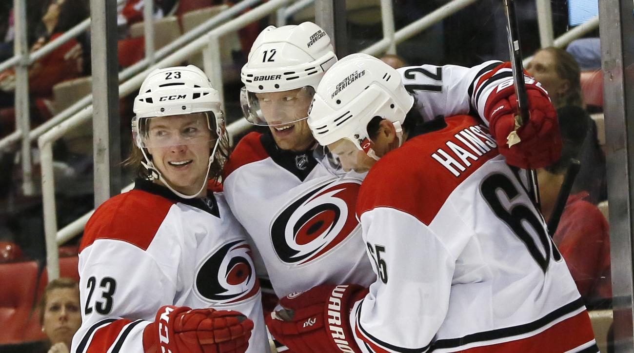 Carolina Hurricanes' Eric Staal (12) celebrates his second-period goal against the Detroit Red Wings with teammates Brock McGinn (23) and Ron Hainsey (65) during an NHL hockey game Friday, Oct. 16, 2015, in Detroit. (AP Photo/Duane Burleson)