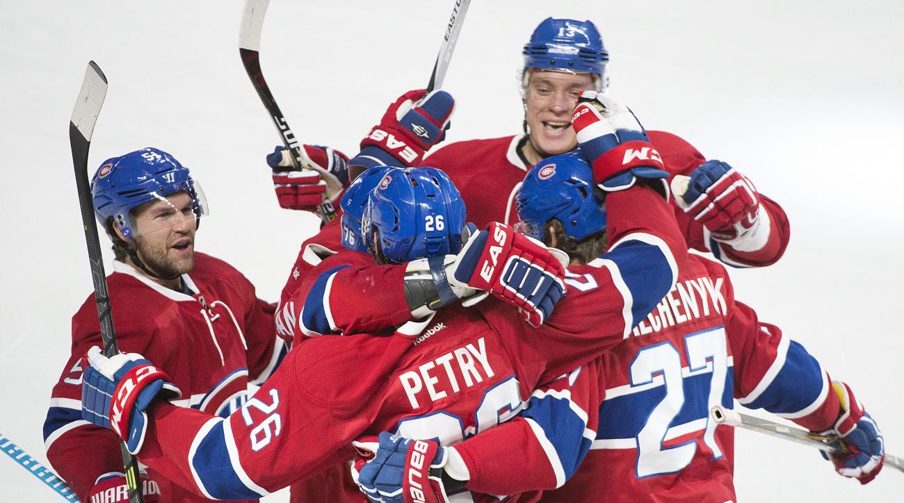 Montreal Canadiens' Jeff Petry (26) celebrates with teammates David Desharnais (51), Alex Galchenyuk (27) and Alexander Semin (13) after scoring against the Detroit Red Wings during third period NHL hockey action in Montreal, Saturday, Oct. 17, 2015. (Gra