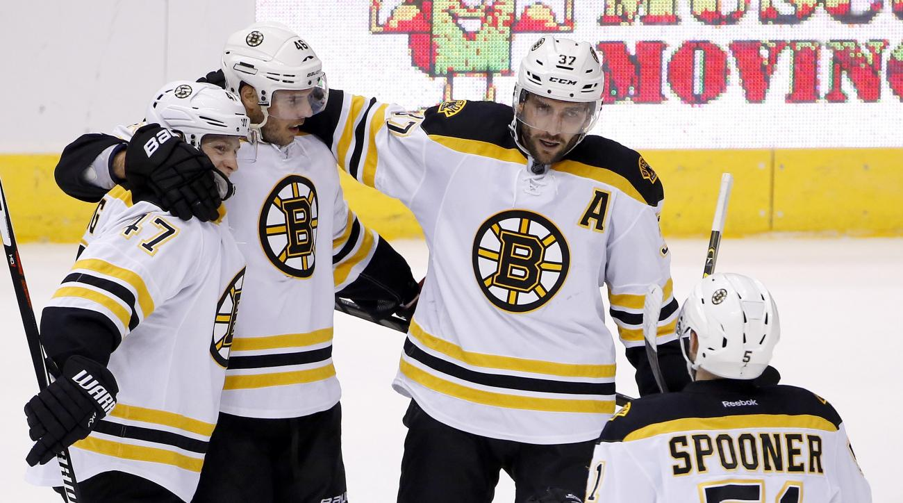 Boston Bruins' David Krejci (46), of the Czech Republic, celebrates his goal against the Arizona Coyotes with Torey Krug (47), Patrice Bergeron (37) and Ryan Spooner (51) during the second period of an NHL hockey game Saturday, Oct. 17, 2015, in Glendale,