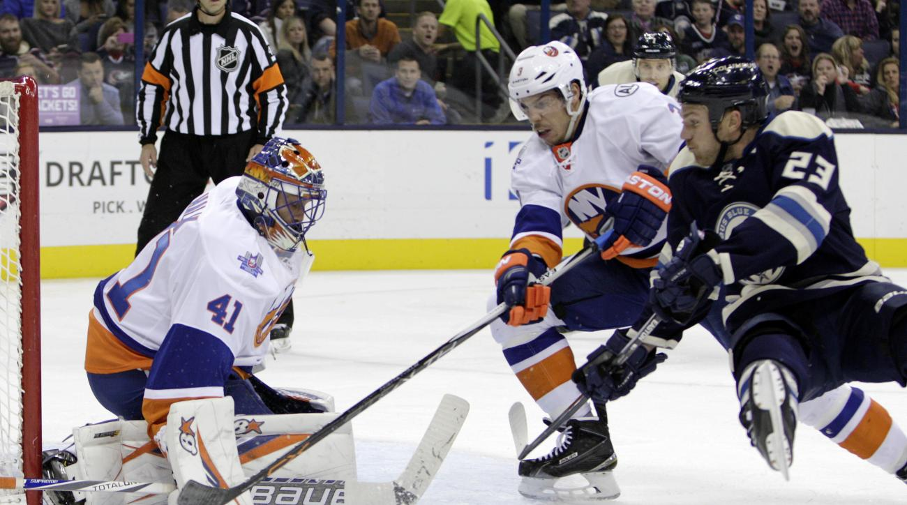 New York Islanders' Jaroslav Halak, left, of Slovakia, makes a save as teammate Travis Hamonic, center, and Columbus Blue Jackets' David Clarkson fight for position during the second period of an NHL hockey game Tuesday, Oct. 20, 2015, in Columbus, Ohio.