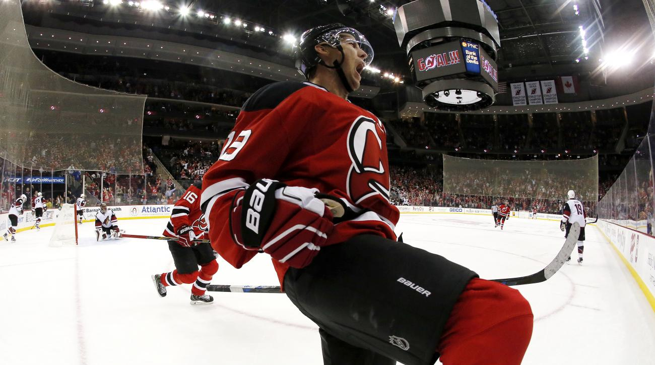 In a photograph taken with a fisheye lens, New Jersey Devils center Travis Zajac celebrates after scoring a goal against the Arizona Coyotes during the second period of an NHL hockey game, Tuesday, Oct. 20, 2015, in Newark, N.J. (AP Photo/Julio Cortez)