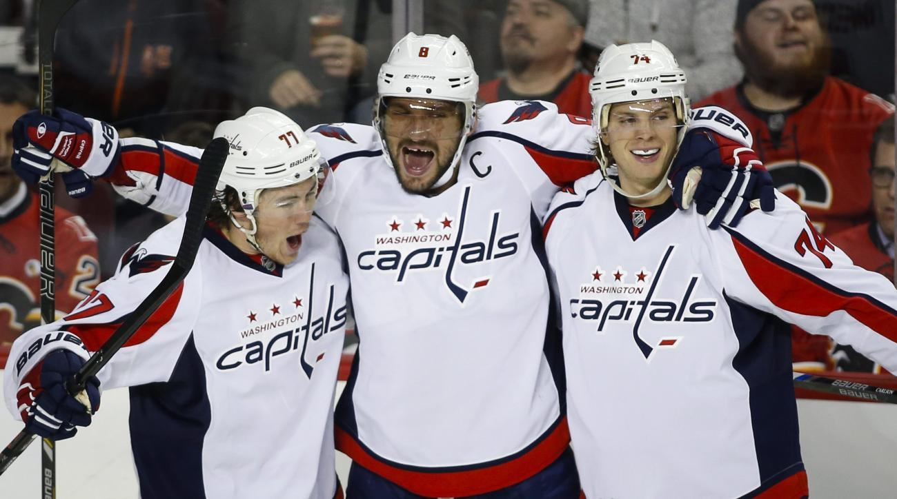 Washington Capitals' Alex Ovechkin, center, from Russia, celebrates his goal with teammates T. J. Oshie, left, and John Carlson during the second period of an NHL hockey game in Calgary, Alberta, Tuesday, Oct. 20, 2015.(Jeff McIntosh/The Canadian Press vi