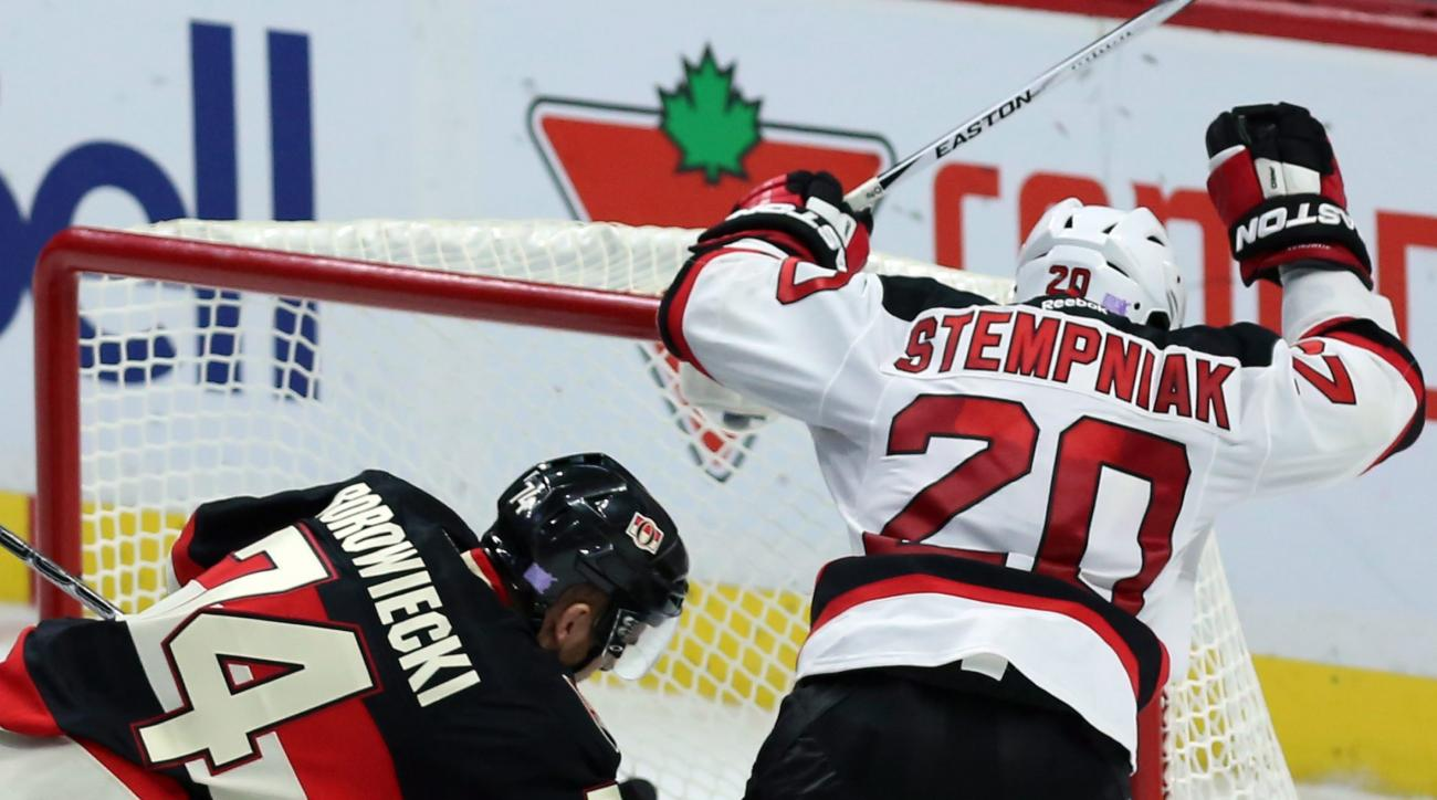 New Jersey Devils' Lee Stempniak, right, celebrates his tying goal as Ottawa Senators' Mark Borowiecki (74) defends during the third period of an NHL hockey game, Thursday, Oct. 22, 2015 in Ottawa, Ontario. The Devils defeated the Senators 5-4. (Fred Char