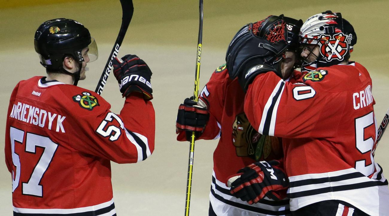 Chicago Blackhawks goalie Corey Crawford, right, celebrates with right wing Andrew Shaw, center, and defenseman Trevor van Riemsdyk after they defeated the Florida Panthers 3-2 in an NHL hockey game Thursday, Oct. 22, 2015, in Chicago. (AP Photo/Nam Y. Hu