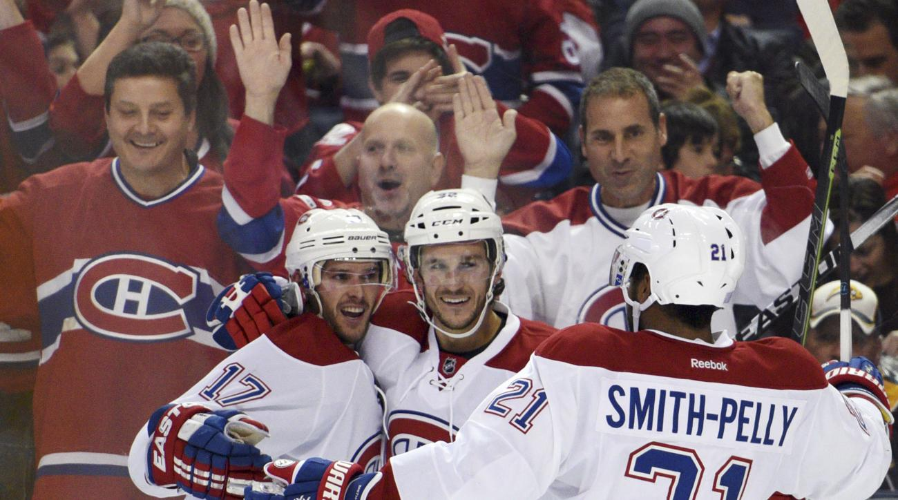 Montreal Canadiens' Torrey Mitchell (17), Brian Flynn (32) and Devante Smith-Pelly (21) celebrate a goal by Mitchell during the second period of an NHL hockey game against the Buffalo Sabres, Friday Oct. 23, 2015 in Buffalo, N.Y. (AP Photo/Gary Wiepert)