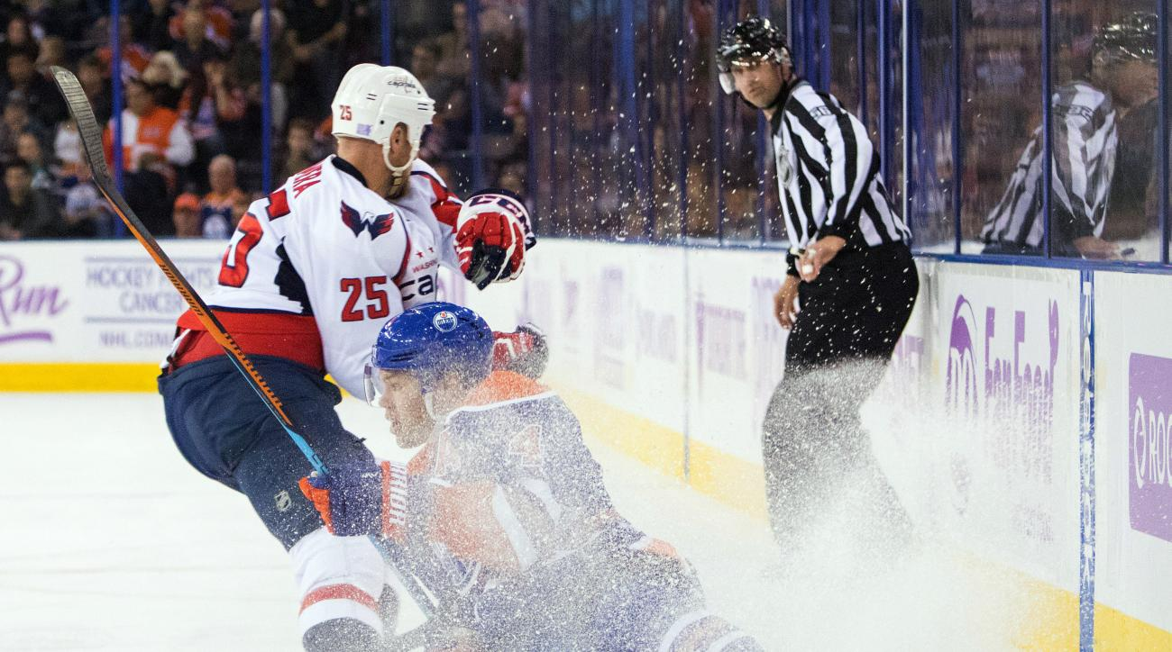 Edmonton Oilers' Taylor Hall (4) falls as he battles Washington Capitals' Jason Chimera (25) during second-period NHL hockey game action in Edmonton, Aberta, Friday, Oct. 23, 2015. (Amber Bracken/The Canadian Press via AP) MANDATORY CREDIT