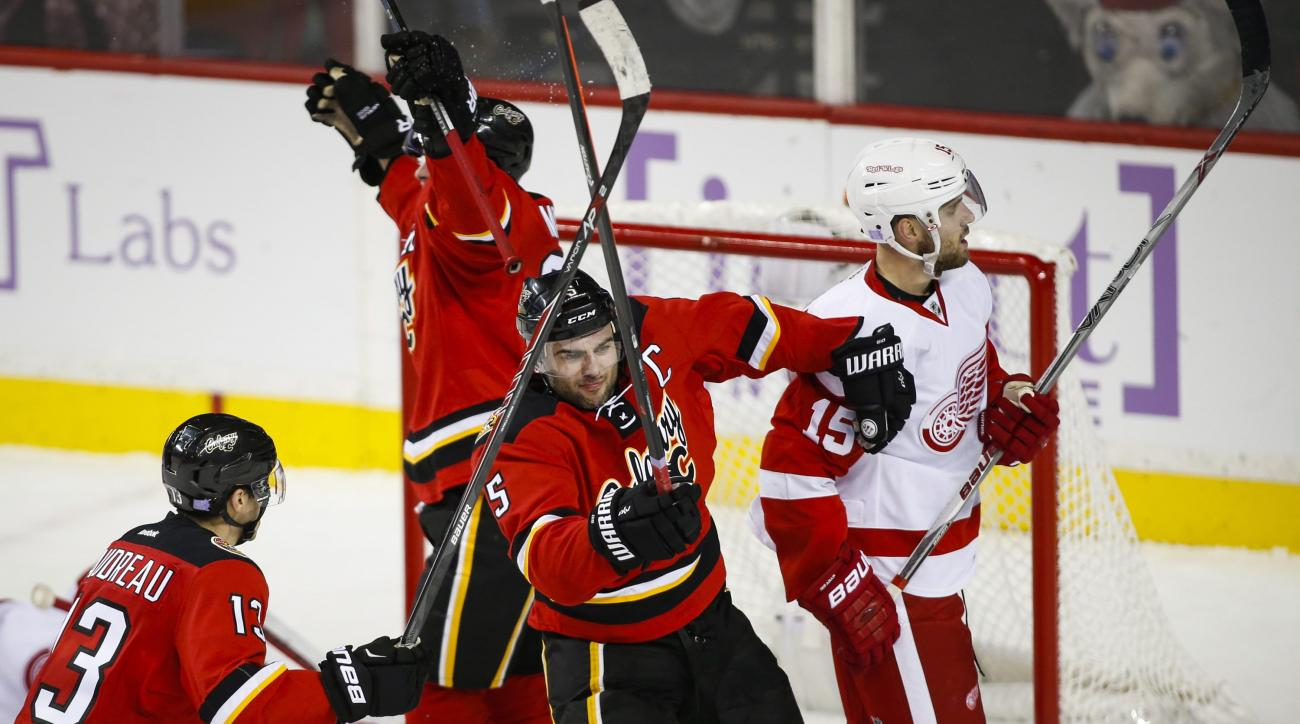Detroit Red Wings' Riley Sheahan, right, skates away as Calgary Flames' Mark Giordano, center, celebrates his game-winning goal in overtime during an NHL hockey game in Calgary, Alberta, Friday, Oct. 23, 2015. Calgary won 3-2. (Jeff McIntosh/The Canadian