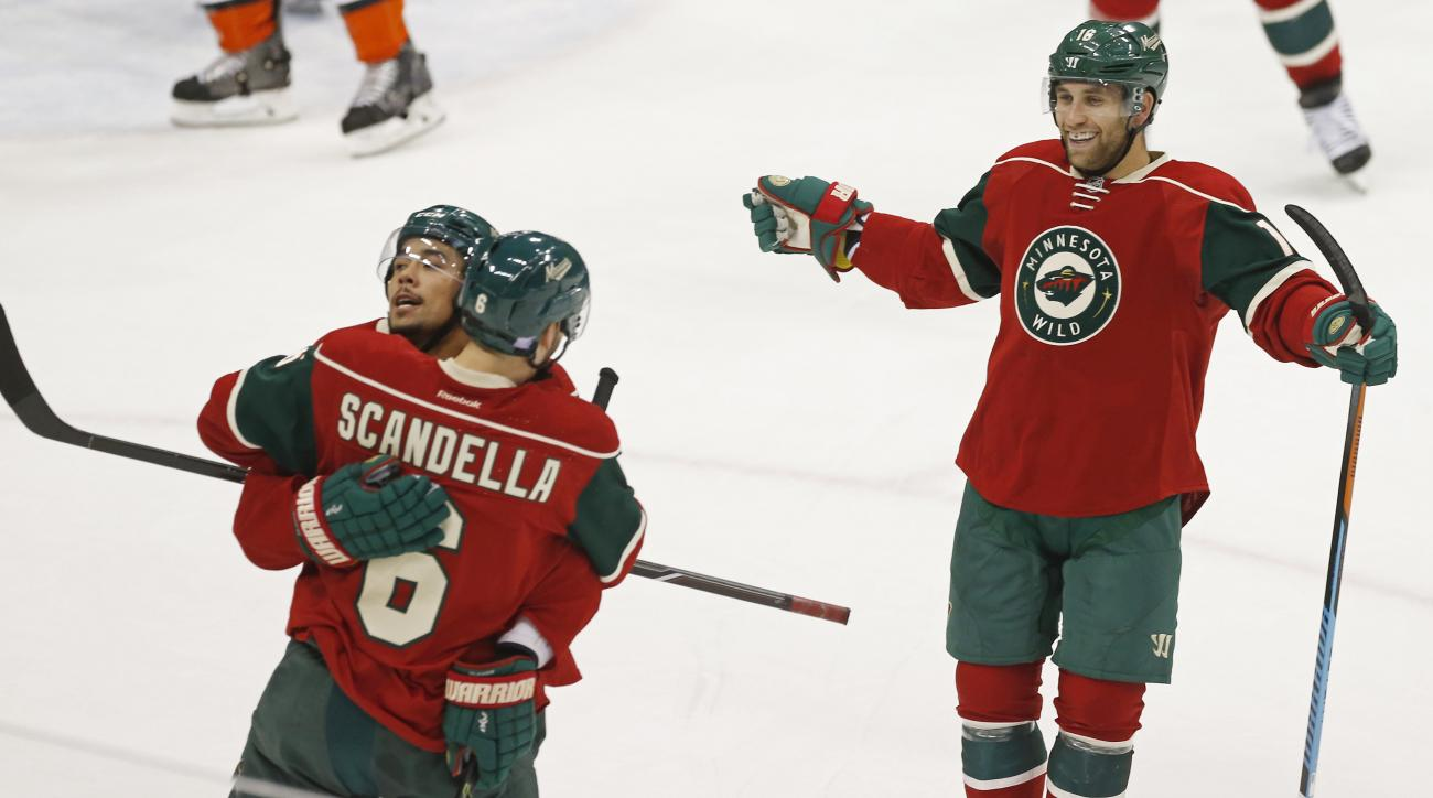 Minnesota Wild's Matt Dumba, left, is congratulated by Marco Scandella as Jason Zucker, right, skates in after Dumba  scored off Anaheim Ducks goalie Frederik Andersen of Denmrk in the first period of an NHL hockey game, Saturday, Oct. 24, 2014, in St. Pa