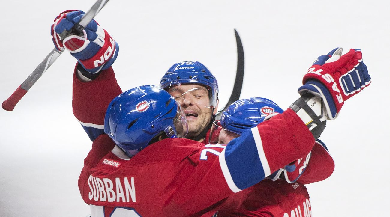 Montreal Canadiens' Brendan Gallagher (11) celebrates with teammates Andrei Markov, center, and P.K. Subban, left, after scoring against the Toronto Maple Leafs during the second period of an NHL hockey game in Montreal, Saturday, Oct. 24, 2015. (Graham H